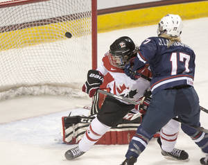 Photo - United States' Jocelyne Lamoureux scores in the second period as Canada's Lauriane Rougeau defends during an exhibition hockey game Friday, Dec. 20, 2013, Grand Forks, N.D. (AP Photo/Grand Forks Herald, Eric Hylden)
