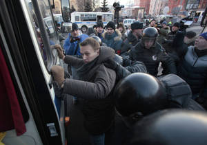 photo - Police officers detain opposition leader Alexei Navalny during an unauthorized rally in Lubyanka Square in Moscow, Saturday, Dec. 15, 2012. Thousands of opposition supporters have gathered in central Moscow for an unauthorized rally where several prominent opposition figures have been detained.(AP Photo/Pavel Golovkin)