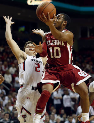 Photo - OU's Jordan Woodard tries to score while being defended by Texas Tech's Dusty Hannahs during Saturday's game. Woodard had 15 points and eight assists in the Sooners' 74-65 win. AP Photo