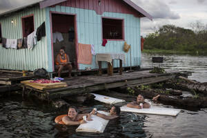 Photo - In this May 18, 2014 photo, residents use refrigerator doors as floating tables outside their floating house on the Rio Negro in Cacau Pirera, near Manaus, Brazil. A World Cup host city, Manaus' far-flung location in the heart of the world's biggest rainforest makes it reachable only by plane or boat. Thousands of foreigners are expected to begin arriving in the Amazonian metropolis for the international soccer matches being held in Manaus's new multi-million dollar soccer stadium. (AP Photo/Felipe Dana)