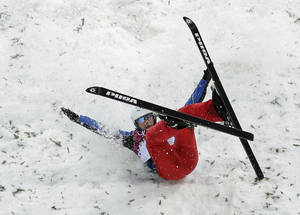Photo - China's Liu Zhongqing crashes upon landing during men's freestyle skiing aerials qualifying at the Rosa Khutor Extreme Park, at the 2014 Winter Olympics, Monday, Feb. 17, 2014, in Krasnaya Polyana, Russia.(AP Photo/Charlie Riedel)
