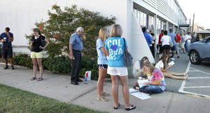 Photo - People wait outside the Department of Motor Vehicles about 6:45 July 20 in Edmond. Some arrived at 4 a.m. to begin the wait. By Paul Hellstern, The Oklahoman <strong>PAUL HELLSTERN</strong>
