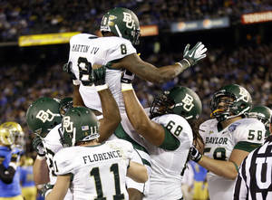 Photo - Baylor running back Glasco Martin is lifted by teammates after scoring a touchdown against UCLA during the first half of the NCAA college football Holiday Bowl game, Thursday Dec. 27, 2012, in San Diego. (AP Photo/Lenny Ignelzi)