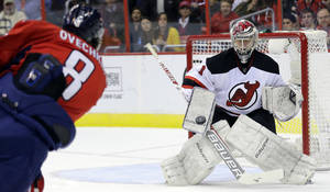 Photo - New Jersey Devils goalie Johan Hedberg (1), from Sweden, blocks a shot by Washington Capitals left wing Alex Ovechkin (8), from Russia, during the first period of an NHL hockey game Saturday, Feb. 23, 2013 in Washington. (AP Photo/Alex Brandon)