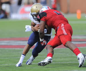 Photo - Western Kentucky Hilltoppers linebacker Andrew Jackson (4) hits Navy Midshipmen quarterback Keenan Reynolds (19) during the first half of an NCAA college football game on Saturday, Sept. 28, 2013, in Bowling Green, Ky. Reynolds would leave the game and not return after the hit. (AP Photo/Joe Imel)