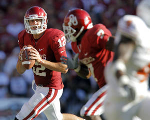 Photo - Oklahoma's Landry Jones (12) looks to throw the ball to DeMarco Murray (7) in the second half of the Red River Rivalry college football game between the University of Oklahoma Sooners (OU) and the University of Texas Longhorns (UT) at the Cotton Bowl on Saturday, Oct. 2, 2010, in Dallas, Texas.   Photo by Chris Landsberger, The Oklahoman