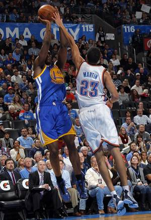 photo - Oklahoma City 's Kevin Martin (23) blocks a shot by Golden State's Harrison Barnes (40) during an NBA basketball game between the Oklahoma City Thunder and the Golden State Warriors at Chesapeake Energy Arena in Oklahoma City, Sunday, Nov. 18, 2012.  Photo by Garett Fisbeck, The Oklahoman