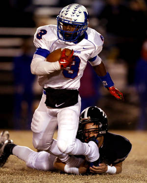 Photo - Millwood's Cameron Batson is brought down by Michael Moore as the Millwood Falcons play the Meeker Bulldogs in state high school football playoffs on Friday, Nov. 29, 2013, in Meeker, Okla.  Photo by Steve Sisney, The Oklahoman