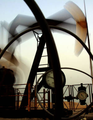 Photo - In this file photo, an oil pump works in the Persian Gulf desert oil fields of Sakhir, Bahrain. The price of oil plunged below $100 per barrel for the first time in more than two months, and a drop in gasoline prices can't be far behind.  (AP Photo/Hasan Jamali, File) ORG XMIT: NY122 <strong>Hasan Jamali - AP</strong>