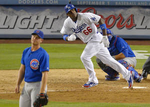 Photo - Los Angeles Dodgers' Yasiel Puig, center, hits a solo home run as Chicago Cubs relief pitcher Michael Bowden, left, and catcher Welington Castillo look on during the eighth inning of their baseball game, Monday, Aug. 26, 2013, in Los Angeles.  (AP Photo/Mark J. Terrill)