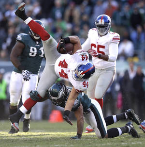 Photo - New York Giants running back Peyton Hillis (44) is tackled by Philadelphia Eagles' Mychal Kendricks (95) during the second half of an NFL football game Sunday, Oct. 27, 2013 in Philadelphia. The Giants won the game 15-7. (AP Photo/Matt Rourke)