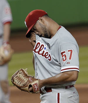 Photo - Philadelphia Phillies relief pitcher Luis Garcia  wipes his face after giving up a base hit to Miami Marlins' Jarrod Saltalamacchia in the eighth inning of a baseball game in Miami, Wednesday, May 21, 2014. The Marlins won 14-5. (AP Photo/Alan Diaz)