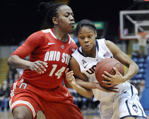 Photo - Connecticut's Moriah Jefferson, right, drives to the basket while guarded by Ohio State's Ameryst Alston, left, during the second half of an NCAA college basketball game Sunday, Dec. 1, 2013, in Springfield, Mass. Connecticut won 70-49. (AP Photo/Jessica Hill)