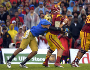 Photo -   UCLA linebacker Anthony Barr, left, sacks Southern California quarterback Matt Barkley during the second half of their NCAA college football game, Saturday, Nov. 17, 2012, in Pasadena, Calif. UCLA won 38-28. (AP Photo/Mark J. Terrill)
