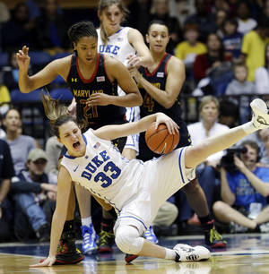 photo - Duke's Haley Peters (33) falls as Maryland's Tianna Hawkins (21) defends during the second half of an NCAA college basketball game in Durham, N.C., Monday, Feb. 11, 2013. Duke won 71-56. (AP Photo/Gerry Broome)