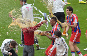 Photo - Bayern head coach Pep Guardiola of Spain, right, gets a shower of beer from Jerome Boateng, center,  after Bayern Munich became the new Bundesliga champion after the German first division Bundesliga soccer match  between FC Bayern Munich and VfB Stuttgart in the Allianz Arena in Munich, Germany, on Saturday, May 10. 2014. (AP Photo/Kerstin Joensson)