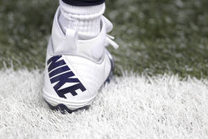 photo - This Dec. 16, 2012 photo shows a Nike shoe worn by a St. Louis Rams football player during the first quarter of an NFL football game between the St. Louis Rams and the Minnesota Vikings in St. Louis. Strong demand in North America helped Nike post second-quarter net income that beat expectations Thursday, Dec. 20, 2012, despite weaker sales in China and costs related to the sale of two brands. (AP Photo/Seth Perlman)