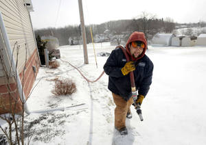 Photo - Denver Walker of Somerset Fuels, makes a heating oil delivery to a home in Jenner Crossroads, Somerset County, PA., Tues., Jan.7, 2014. Walker said he is very busy this week. (AP Photo/Tribune-Democrat, John Rucosky).