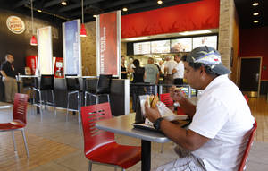 Photo -   In this March 28, 2012 photo, Norman Garcia eats a burger and fries at a Burger King restaurant in Miami. Burger King launches 10 menu items including smoothies, frappes, specialty salads and snack wraps in a star-studded TV ad campaign. It's the biggest menu expansion since the chain opened its doors in 1954. (AP Photo/Luis M. Alvarez)