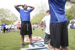 Photo - NFL Draft prospect Russell Okung, left, of Oklahoma State, watches youngsters run drills during a youth  clinic at Central Park in New York on Wednesday. AP Photo