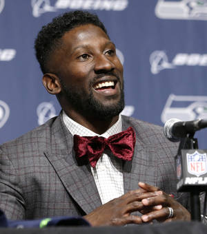 Photo - Seattle Seahawks' Marcus Trufant smiles during a news conference announcing his retirement from football after signing with the team a day earlier, Thursday, April 24, 2014, in Renton, Wash. Trufant started 125 games in a Seattle career that lasted from 2003 to 2012. The cornerback was a first-round pick in 2003 out of Washington State and immediately moved into the starting lineup, playing a key role on the 2005 team that advanced to the franchise's first Super Bowl. (AP Photo/Elaine Thompson)
