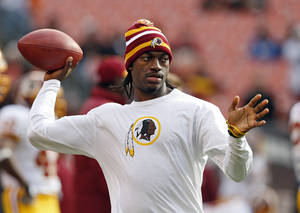 Photo - Washington Redskins quarterback Robert Griffin III tosses a ball during warmups before an NFL football game against the Cleveland Browns in Cleveland, Sunday, Dec. 16, 2012. Kirk Cousins will start in place of Griffin wgho is sitting out with a sprained knee. (AP Photo/Rick Osentoski)