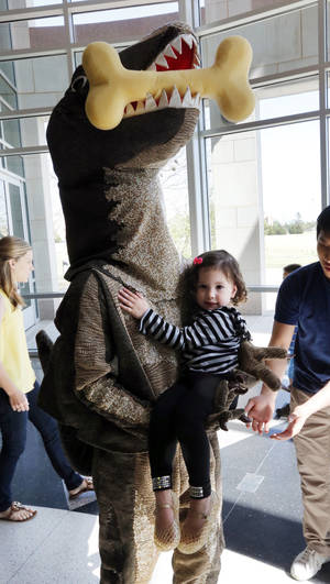 Photo -  Cambelle Ho, 3, cozys up to Slash the dinosaur during this year's Eggstravaganza at the Sam Noble Oklahoma Museum of Natural History. Eggstravaganza is just one of the many community programs sponsored by the museum each year. PHOTO BY STEVE SISNEY, THE OKLAHOMAN  <strong>STEVE SISNEY -   </strong>