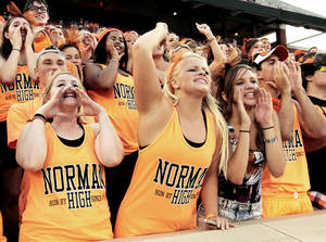 Photo - Norman High School fans Rebekah Abbott, Kaylea Fabri  and Savannah Piper cheer as their Tigers play Norman North Timberwolves at Gaylord Family-Oklahoma Memorial Stadium in Norman, Okla., on Thursday, Sept. 5, 2013. Photo by Steve Sisney, The Oklahoman