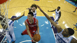 Photo -   Houston Rockets point guard Jeremy Lin, center front, drives to the basket between New Orleans Hornets small forward Lance Thomas (42), center Robin Lopez (15) and power forward Anthony Davis (23) in the first half of a preseason NBA basketball game in New Orleans, Wednesday, Oct. 24, 2012. (AP Photo/Gerald Herbert)