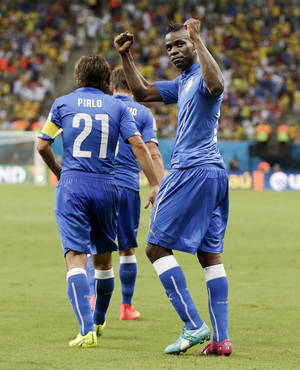 Photo - Italy's Mario Balotelli, right, gestures to the crowd after scoring his side's second goal during the group D World Cup soccer match between England and Italy at the Arena da Amazonia in Manaus, Brazil, Saturday, June 14, 2014.(AP Photo/Marcio Jose Sanchez)