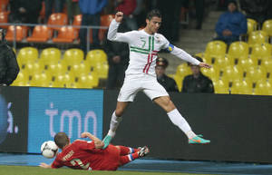 Photo -   Portugal's Cristiano Ronaldo jumps over Russia's Aleksandr Anyukov, bottom, in their World Cup 2014 Group F qualification match at Luzhniki stadium in Moscow, Russia, on Friday, Oct. 12, 2012. (AP Photo/Mikhail Metzel)
