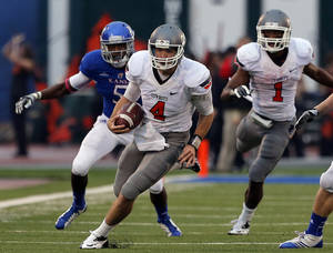 Photo - Oklahoma State's J.W. Walsh (4) rushes during the college football game between Oklahoma State University (OSU) and the University of Kansas (KU) at Memorial Stadium in Lawrence, Kan., Saturday, Oct. 13, 2012. Photo by Sarah Phipps, The Oklahoman