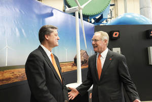 Photo - Oklahoma Gas and Electric President Peter Delaney, left, and Oklahoma State University President Burns Hargis speak Friday before a ceremony marking the completion of a 60-megawatt wind farm near Blackwell that will help supply electricity to the OSU campus in Stillwater.  Photo By Paul Hellstern, The Oklahoman