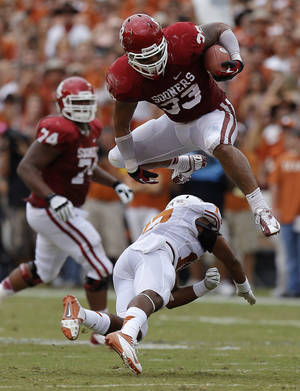photo - OU's Trey Millard (33) leaps over UT's Adrian Phillips (17) during the Red River Rivalry college football game between the University of Oklahoma (OU) and the University of Texas (UT) at the Cotton Bowl in Dallas, Saturday, Oct. 13, 2012. Photo by Bryan Terry, The Oklahoman