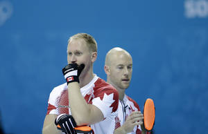 Photo - Canada's skip, Brad Jacobs, left, and Ryan Fry, right, wait for their turn to curl during the men's curling competition against Germany at the 2014 Winter Olympics, Monday, Feb. 10, 2014, in Sochi, Russia. (AP Photo/Wong Maye-E)