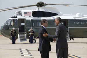 Photo - President Barack Obama is greeted by Texas Gov. Rick Perry as he arrives at Dallas/Fort Worth International Airport, Wednesday, July 9, 2014. The president is expected to attend a meeting on immigration, (AP Photo/Jacquelyn Martin)