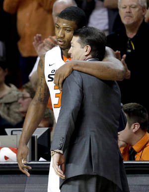 Photo - Oklahoma State's Marcus Smart (33) hugs Oklahoma State head coach Travis Ford in final minutes of the men's college basketball game between Oklahoma State and Texas Tech at Gallagher-Iba Arena in Stillwater, Okla., Saturday, Feb. 22, 2014. OSU won 84-62. 