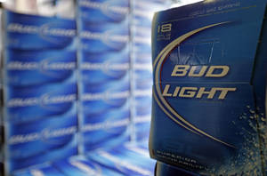 photo - FILE - In this Monday, Jan. 28, 2013, file photo, Bud Light beer is shown in the aisles of Elite Beverages in Indianapolis. Beer lovers across the country have filed $5 million class-action lawsuits accusing Anheuser-Busch of watering down its Budweiser, Michelob and other brands.  (AP Photo/Michael Conroy, File)