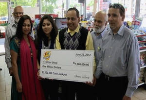 photo - This June 2012 photo provided by WMAQ-TV in Chicago shows Urooj Khan, center, holding a ceremonial check in Chicago for $1 million as winner of an Illinois instant lottery game. At left, is Khan's wife, Shabana Ansari. Khan, 46, who owned several dry cleaning operations and some real estate, died suddenly on July 20, 2012, just days before he was to collect his winnings. Khan's death has been ruled a homicide. Court records show that Ansari has battled with his siblings over control of his estate, including his $425,000 prize money. A Cook County judge on Friday, Jan. 11, 2013, approved the exhumation of Khan's body. (AP Photo/Courtesy of WMAQ-TV in Chicago)