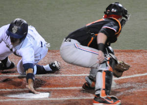 Photo - UC Irvine's Chris Rabago gets his hand on the plate as he scores the third run of the inning for the Anteaters in front of Oregon State catcher Logan Ice during an NCAA college baseball regional tournament game in Corvallis, Ore., Saturday, May 31, 2014. (AP Photo/Mark Ylen)
