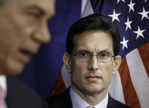 Photo - House Majority Leader Eric Cantor of Va., listens at right as House Speaker John Boehner of Ohio, during a news conference on Capitol Hill in Washington, Tuesday, June 10, 2014. Cantor faces a challenge from a political newcomer backed by the tea party as Virginia voters go to the polls Tuesday for three congressional primaries. Cantor was once popular in the tea party but has now become its target.  (AP Photo/J. Scott Applewhite)