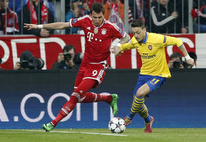 Photo - Bayern's Mario Mandzukic, left, and Arsenal's Mesut Ozil challenge for the ball during the Champions League round of 16 second leg soccer match between FC Bayern Munich and FC Arsenal in Munich, Germany, Tuesday, March 11, 2014. (AP Photo/Matthias Schrader)