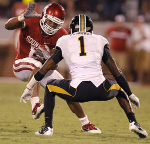 Photo - Oklahoma's Dominique Whaley (8) tries to get past Missouri's Kip Edwards (1) during the college football game between the University of Oklahoma Sooners (OU) and the University of Missouri Tigers (MU) at the Gaylord Family-Memorial Stadium on Saturday, Sept. 24, 2011, in Norman, Okla. Photo by Chris Landsberger, The Oklahoman