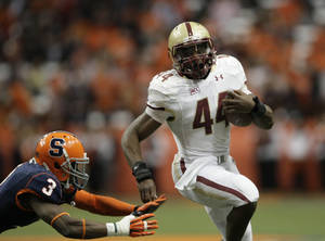 Photo - Boston College's Andre Williams, right, runs past Syracuse's Durell Eskridge for a touchdown in the first quarter of an NCAA college football game in Syracuse, N.Y., Saturday, Nov. 30, 2013. (AP Photo/Nick Lisi)