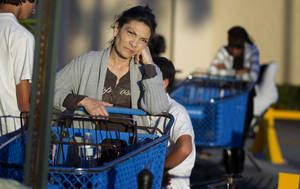 photo -   Dora Hurtado waits in line at a Pembroke Pines, Fla. Toys-R-Us store, late Friday, Nov. 22, 2012. While stores typically open in the wee hours of the morning on the day after Thanksgiving known as Black Friday, openings have crept earlier and earlier over the past few years. Now, stores from Wal-Mart to Toys R Us are opening their doors on Thanksgiving evening, hoping Americans will be willing to shop soon after they finish their pumpkin pie. (AP Photo/J Pat Carter)