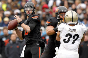 photo - Oklahoma State's Clint Chelf (10) drops back to pass during the Heart of Dallas Bowl football game between Oklahoma State University and Purdue University at the Cotton Bowl in Dallas, Tuesday, Jan. 1, 2013. Oklahoma State won 58-14. Photo by Bryan Terry, The Oklahoman