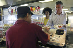 Photo - Democratic mayoral hopeful Bill de Blasio, right, and his son Dante pay for popcorn and a hotdog they purchased from the concession stand on the Staten Island ferry, Wednesday, Sept. 4, 2013 in New York.  (AP Photo/Mary Altaffer)