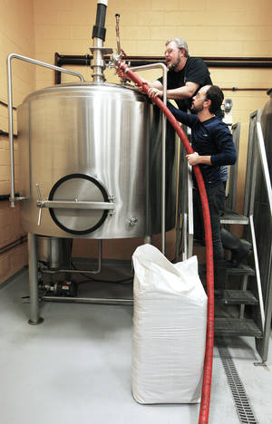 photo - Mustang Brewing Co. brewmaster Gary Shellman, top, and assistant Eric Pennell work on a tank brewing beer at the OKCity Brewing Cooperative.