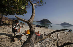 Photo - In this Sunday, Feb. 9, 2014 photo, a woman belonging to Moken tribe, nomads of the sea, cooks food in the shade of a tree on Island 115 in Mergui Archipelago, Myanmar. Isolated for decades by the country's former military regime and piracy, the Mergui archipelago is thought by scientists to harbor some of the world's most important marine biodiversity and looms as a lodestone for those eager to experience one of Asia's last tourism frontiers before, as many fear, it succumbs to the ravages that have befallen many of the continent's once pristine seascapes. (AP Photo/Altaf Qadri)