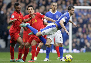 Photo -   Everton's Kevin Mirallas, right, is felled by Liverpool's Nuri Sahin, centre left, as Raheem Sterling, left, and Leon Osman looks on, during their English Premier League soccer match at Goodison Park Stadium, Liverpool, England, Sunday, Oct. 28, 2012. (AP Photo/Jon Super)